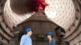 Ein Mann und eine Frau mit blauen Arbeitshelmen stehen in einem Gebäude mit Kuppeldach.