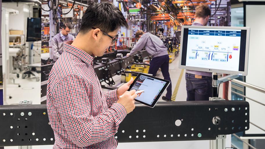 Ein Mann arbeitet in einer Produktionshalle an einem Tablet.