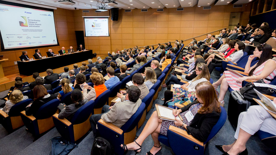 Menschen sitzen in einem Hörsaal bei einer Konferenz.