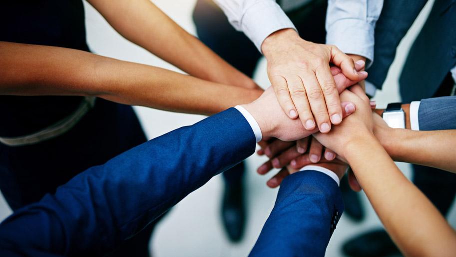 Die Händer verschiedener Menschen stapeln sich in der Mitte zu einem Kreis.