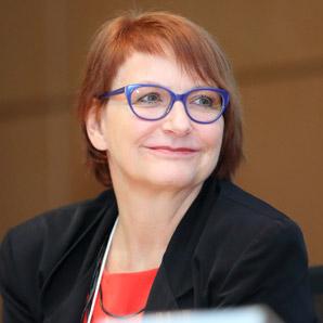 Eine Frau mit Brille lächelt.